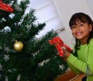Daugther décorant un arbre de Noël Image stock