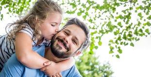 Daugther geeft vader een kus stock afbeelding
