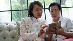 Daugther nauczania matka używać mądrze telefon dla ogólnospołecznych środków przy Obraz Royalty Free