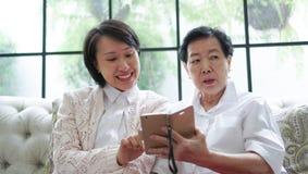 Daugther nauczania matka używać mądrze telefon dla ogólnospołecznych środków przy Obrazy Royalty Free