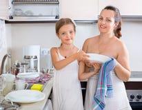 Dauhter die haar moeder met dishwashing helpen Stock Afbeelding