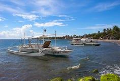 Dauin, Filipiny - 26 Czerwiec, 2016: Morze i łodzie cumowaliśmy blisko brzeg obraz royalty free
