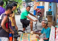 Dauin Filippinerna - 9 September, 2017: Folkvågspel på bygatan Filippino byinvånare Arkivfoto