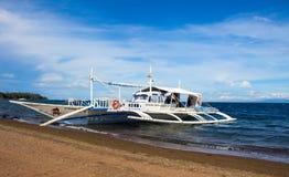 Dauin, Philippines - 1er mars 2017 : Bateau près de la plage Catamaran en bois blanc dans le seav bleu Photo libre de droits