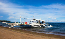Dauin, Philippines - 1 March, 2017: Boat near the beach. White wooden catamaran in blue seav royalty free stock photo