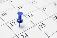 Daumen-Heftzwecke auf Kalender stockfotografie