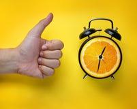 Daumen herauf Hand und Wecker der orange Frucht auf gelbem Backgrou Stockfotos