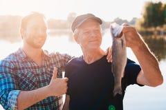Daumen oben Der alte Mann hält einen Fisch Ein Mann steht hinter ihm mit seinem Daumen oben Stockbild