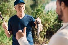 Daumen oben Der alte Mann zeigt dem Mann, einen welchen großen Fisch er fing Lizenzfreie Stockbilder