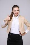 Daumen oben Geschäftsfrau auf grauem Hintergrund Weibliches Modell Lizenzfreie Stockbilder