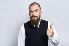Daumen oben Hübscher Geschäftsmann mit dem Bart- und Lenkstangenschnurrbart, der Kamera mit den Daumen oben betrachtet Stockfotografie