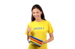 Daumen oben. Schöner Student mit Schweden-Flagge auf der gelben Bluse, die Bücher hält. Stockfotos