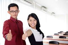 Daumen oben von jungen Geschäftspaaren im Büro Lizenzfreie Stockfotos