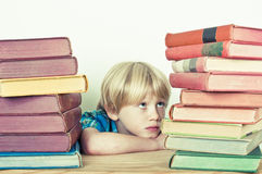 Daunting. Little boy looking at his pile of homework Royalty Free Stock Image