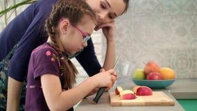 Dauther del learnig de la madre usando el cuchillo Rebanada de la manzana del corte de la niña almacen de video