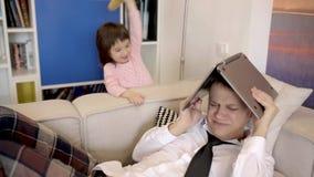 Dauther raakt haar vader met een stuk speelgoed stock video