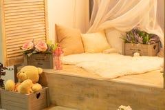 Davanzale con i cuscini, la pelliccia bianca, l'orsacchiotto ed i fiori nessuno fotografie stock
