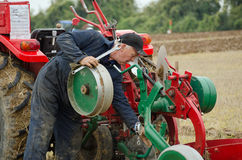 David Chappell making adjustments. BASINGSTOKE, UK - OCTOBER 12, 2014: Competitor David Chappell making adjustments to his plough while competing in the second Stock Photo