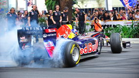David, der Burnouts in Red Bull läuft Auto F1 tut Stockbilder