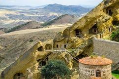 David Gareja Monastery Complex op Georgië een grens van Azerbeidzjan, rode torens, kleurrijke woestijnheuvels op de achtergrond stock foto's