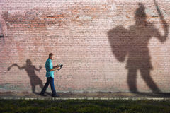 David and Goliath. A man reads a Bible while his shadow is David fighting goliath royalty free stock photos