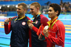 David Plummer of USA, Olympic champion Ryan Murphy of USA and Jiayu Xu of China during medal ceremony after Men`s 100m backstroke. RIO DE JANEIRO, BRAZIL Royalty Free Stock Photos