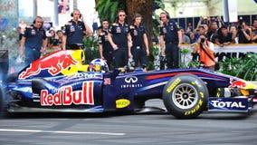 David que hace los anillos de espuma en Red Bull que compite con el coche F1 Imagenes de archivo