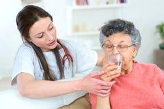 Dawać starszej kobieta napoju wodzie fotografia royalty free