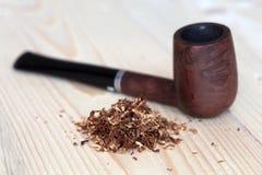 Dawka suchy tytoń i drymba na drewnianym tle Zdjęcia Royalty Free
