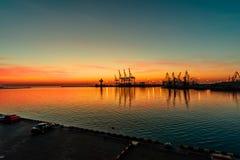 Dawn σε έναν θαλάσσιο λιμένα με έναν πορφυρό κόκκινο νεφελώδη ουρανό και μια αντανάκλαση Στοκ Εικόνα
