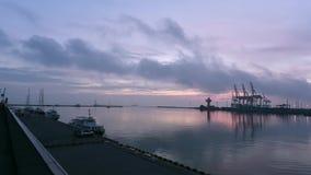 Dawn στο θαλάσσιο λιμένα Η ταλάντευση βαρκών και γιοτ στα κύματα στην αποβάθρα, ένα μεγάλο φορτηγό πλοίο κολυμπά από το λιμένα φιλμ μικρού μήκους