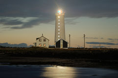 Dawn. Lighthouse that lights up into the water along the beach Royalty Free Stock Photography