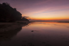 Dawn at beach in Bali, Indonesia. This was shot in dawn, before the sun rise. the beautiful colors of the sky reflected on the smooth water surface accompany by Royalty Free Stock Photos