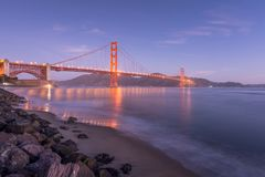 Dawn begins from Fort Point. During low tide it is possible to access the rocky beach and photograph the iconic golden gate bridge at sunrise, as it casts its stock images