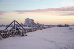 Dawn bij een winterland met een stijl door steenmuur Stock Afbeeldingen