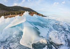 Dawn in the blue hummocks of ice lake baikal, in a snowy field in winter on a journey.  Stock Photos