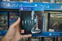 Until Dawn. Bratislava, Slovakia, circa april 2017: Man holding Until Dawn videogame on Sony Playstation 4 console in store Royalty Free Stock Image
