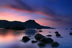 Dawn in a calm bay. Ocean dawn in a quiet cove, a colorful sky over the low mountain Stock Photos