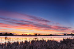 Dawn with colorful clouds over a wild pond in autumn morning Stock Photos