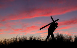 Dawn Cross Carry. Man with a carrying a cross on his back at sunrise Royalty Free Stock Photos