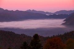 Dawn in de bergen en mist in de vallei Stock Fotografie