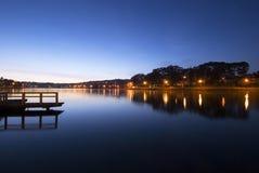 Dawn/dusk at Xuan Huong Lake, Dalat, Vietnam. Blue twilight sky, street lights, quiet surface/lake, a small bridge/wharf Stock Photos