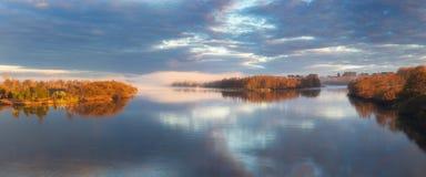 Dawn in een mist op de rivier De herfstochtend Een mist over water De zon in een mist Vroege ochtendzonsopgang gloed en het toene stock foto's
