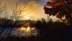 Dawn Exploding på floden arkivbild