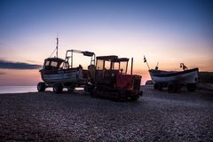 Dawn Glow on Fishing Boats on a Shingle Beach. Fishing boats Anna Gail and Lady Iris catch the light at dawn. The shingle beach at Weybourne on the North Norfolk Royalty Free Stock Photo