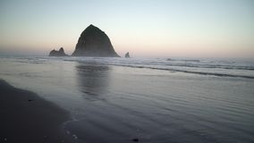 Haystack Rock, Cannon Beach Dawn dolly shot 4K. UHD. Dawn at Haystack Rock in Cannon Beach, Oregon as the surf washes up onto the beach. United States stock video