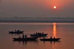 Dawn at Holy Ganges river. People at boats in Holy ganges river enjoying an stunning dawn at ancient Varanasi city in India royalty free stock photography