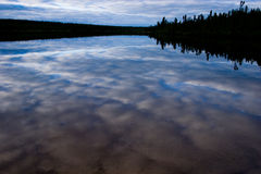 Dawn Lake. Lake found in northern Saskatchewan. Perfect reflection of the clouds and blue sky above stock photography