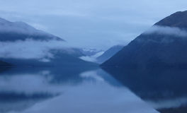 Dawn on Lake Rotoiti. Pre-dawn mist rolls in over Lake Rotoiti, in the Nelson Lakes region in New Zealand's South Island. Mt Robert in the right of the image stock image