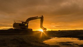 Dawn Light Digging. One larger digger park up waiting for anothers days work stock images